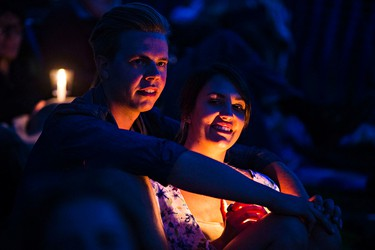 Alex  Kuczera, left, and Katrina Bellefeuille, right, watch as Bear's Den performs during the Edmonton Folk Music Festival at Gallagher Park in Edmonton, Alta. on Saturday, Aug. 8, 2015. Codie McLachlan/Edmonton Sun/Postmedia Network
