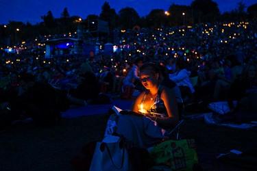 Athena Nash reads by candlelight during the Edmonton Folk Music Festival at Gallagher Park in Edmonton, Alta. on Saturday, Aug. 8, 2015. Codie McLachlan/Edmonton Sun/Postmedia Network