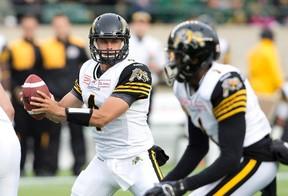 Hamilton Tiger-Cats quarterback Zach Collaros (4) looks for the handoff against the Edmonton Eskimos during first half CFL action in Edmonton, Alta., on Friday August 21, 2015. THE CANADIAN PRESS/Jason Franson.