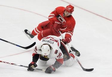 Caroline Hurricanes' John-Michael Liles (top) and Ottawa Senators Zack Stortini collide during an NHL exhibition game in St. John's, N.L, Sunday, Sept.27, 2015. THE CANADIAN PRESS/Keith Gosse