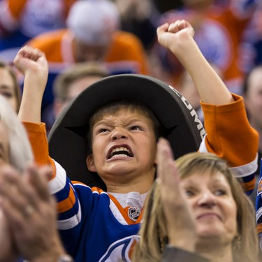 An Edmonton fan celebrates centre Anton Lander's hat trick during the third period of an NHL game between the Edmonton Oilers and the Arizona Coyotes at Rexall Place in Edmonton, Alta. on Tuesday September 29, 2015. Ian Kucerak/Edmonton Sun/Postmedia Network
