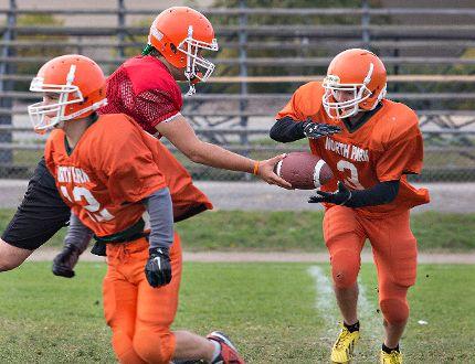 North Park Collegiate quarterback Matt Krason (left) hands off to Brett Stubbert during a senior high school football practice. (BRIAN THOMPSON/The Expositor)
