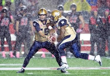 Winnipeg Blue Bombers' quarterback Matt Nichols, left, hands the ball to running back Cameron Marshall during first half CFL action against the Ottawa RedBlacks, in Ottawa, Friday, Oct. 16, 2015. THE CANADIAN PRESS/Adrian Wyld