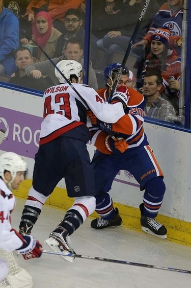 Edmonton Oilers' forward Luke Gazdic (20) is checked by Washington Capital's  Washington Capitals forward Tom Wilson (43) during 2nd period NHL action at Rexall Place in Edmonton, Alberta on October 21, 2015. Perry Mah/Edmonton Sun/Postmedia Network