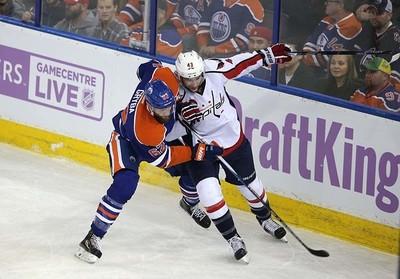 Edmonton Oilers' defensemen Eric Gryba (62)  is checked by  Washington Capital's  Washington Capitals forward Tom Wilson (43) during 1st period NHL action at Rexall Place in Edmonton, Alberta on October 21, 2015. Perry Mah/Edmonton Sun/Postmedia Network