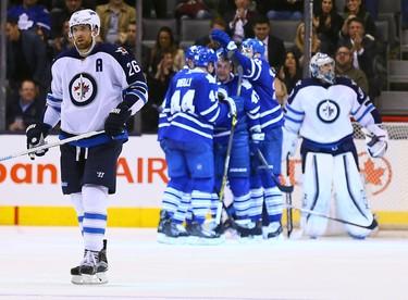 The Toronto Maple Leafs celebrate Leo Komarov goal as Blake Wheeler of the Winnipeg Jets skates to the bench during NHL action at the Air Canada Centre in Toronto on Wednesday November 4, 2015. Dave Abel/Toronto Sun/Postmedia Network