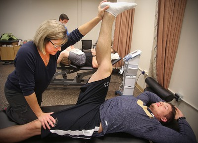 University of Manitoba Bisons head athletic therapist Lori Nickel (l) stretches the leg of  linebacker DJ Lalama Wednesday November 04, 2015 after a knee injury. Brian Donogh/Winnipeg Sun/Postmedia Network