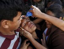 Residents help a relative (C) of a slain victim at a crime scene where seven men were killed, in Tegucigalpa, Honduras, Nov. 25, 2015. REUTERS/Jorge Cabrera