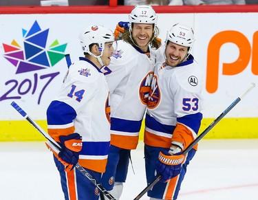 New York IslandersThomas Hickey (14) and Casey Cizikas (53) congratulate teammate Matt Martin (17) on his first period goal against the Ottawa Senators during NHL action in Ottawa, Ont. on Saturday December 5, 2015. Errol McGihon/Ottawa Sun/Postmedia Network