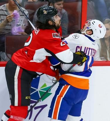 Ottawa Senators defenseman Jared Cowen (2) checks New York Islanders right wing Cal Clutterbuck (15) during NHL action in Ottawa, Ont. on Saturday December 5, 2015. Errol McGihon/Ottawa Sun/Postmedia Network