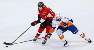 Ottawa Senators center Zack Smith (15) keeps the puck away from New York Islanders defenseman Nick Leddy (2) during NHL action in Ottawa, Ont. on Saturday December 5, 2015. Errol McGihon/Ottawa Sun/Postmedia Network