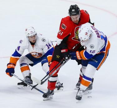 Ottawa Senators right wing Mark Stone (61) gets tied up by  New York Islanders defenseman Thomas Hickey (14) and Josh Bailey (12) during NHL action in Ottawa, Ont. on Saturday December 5, 2015. Errol McGihon/Ottawa Sun/Postmedia Network