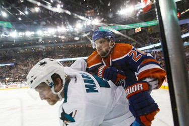 Edmonton forward Iiro Pakarinen (26) checks San Jose defenceman Paul Martin (7) during the third period of a NHL game between the Edmonton Oilers and the San Jose Sharks at Rexall Place in Edmonton, Alta. on Wednesday December 9, 2015. Ian Kucerak/Edmonton Sun/Postmedia Network