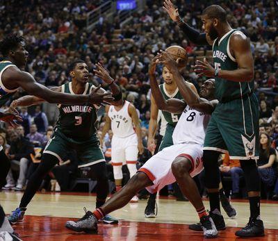 Toronto Raptors Bismack Biyombo  battles for the ball against  Milwaukee Bucks O.J. Mayo  in Toronto, Ont. on Friday December 11, 2015. Craig Robertson/Toronto Sun/Postmedia Network