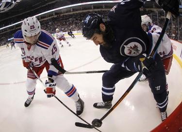 New York Rangers' Viktor Stalberg (25) battles with Winnipeg Jets' Chris Thorburn (22) during second period NHL hockey action in Winnipeg, Friday, December 18, 2015. Image taken with a fisheye lens. THE CANADIAN PRESS/Trevor Hagan