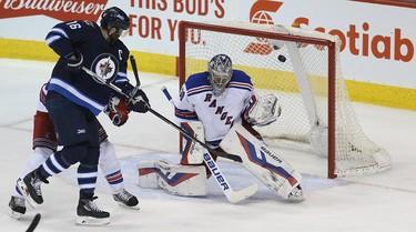 New York Rangers goaltender Henrik Lundqvist is beaten by Winnipeg Jets defenceman Tyler Myers (not shown) as Andrew Ladd causes havoc in the crease in Winnipeg on Fri., Dec. 18, 2015. Kevin King/Winnipeg Sun/Postmedia Network