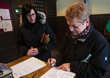 Christine Armitage, left, looks on as her mother, Sandi Armitage, right, writes with a fountain pen during Fort Edmonton Park's Christmas Reflections in Edmonton, Alta., on Sunday, Dec. 20, 2015. Codie McLachlan/Edmonton Sun/Postmedia Network