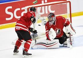 Canada's goalie Mason McDonald and Joe Hicketts, left, watch the puck fly into the net during world junior play against the U.S.A. in Helsinki Saturday, Dec. 26, 2015. (Roni Rekomaa/Lehtikuva via AP)