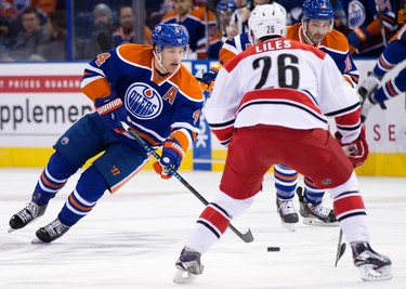 The Edmonton Oilers' Taylor Hall (4) battles the Carolina Hurricanes John-Michael Liles (26) during first period NHL action at Rexall Place, in Edmonton Alta. on Monday Jan. 4, 2016. David Bloom/Edmonton Sun/Postmedia Network