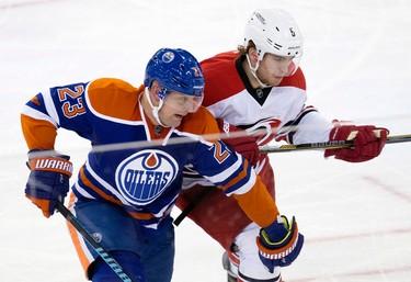 The Edmonton Oilers' Matt Hendricks (23) battles the Carolina Hurricanes Noah Hanifin (5) during third period NHL action at Rexall Place, in Edmonton Alta. on Monday Jan. 4, 2016. The Oilers won 1-0 in overtime. David Bloom/Edmonton Sun/Postmedia Network