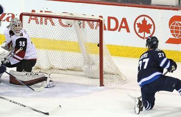 Winnipeg Jets right winger Nikolaj Ehlers (r) gets the puck past Arizona Coyotes goalie Louis Dominigue during NHL hockey in Winnipeg, Man. Tuesday January 26, 2016. Brian Donogh/Winnipeg Sun/Postmedia Network