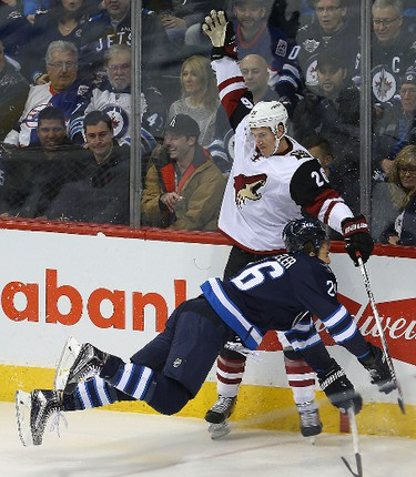 Winnipeg Jets right winger Blake Wheeler is dumped by Arizona Coyotes defenceman Michael Stone during NHL hockey in Winnipeg, Man. Tuesday January 26, 2016. Brian Donogh/Winnipeg Sun/Postmedia Network
