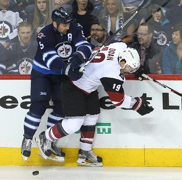 Winnipeg Jets defenceman Mark Stuart (l) checks Arizona Coyotes right winger Shane Doan during NHL hockey in Winnipeg, Man. Tuesday January 26, 2016. Brian Donogh/Winnipeg Sun/Postmedia Network