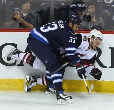 Winnipeg Jets defenceman Dustin Byfuglien (l) checks Arizona Coyotes left winger Max Domi during NHL hockey in Winnipeg, Man. Tuesday January 26, 2016. Brian Donogh/Winnipeg Sun/Postmedia Network