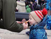 Ernie Leiliunas let his son Duncan try a Beavertail at FebFest in Springer Market Square in Kingston, Ont. on Saturday February 6, 2016. Steph Crosier/Kingston Whig-Standard/Postmedia Network
