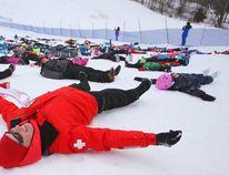 Ski patrol member Christian Balayer makes snow angels with 182 other patrollers and citizens Saturday at Batawa Ski Hill.