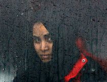 A migrant looks through a train window