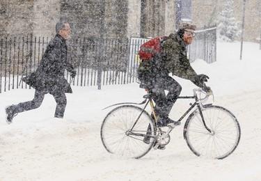 A cyclist and pedestrian cross Elgin Street in Ottawa during a major snowfall on Thursday January 21, 2016. Errol McGihon