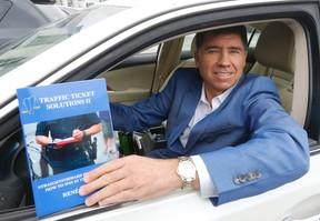 Realtor Rene Papa holds his latest book on how to fight traffic tickets. (Michael Peake/Toronto Sun)