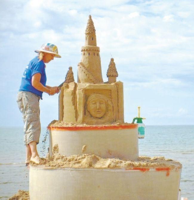 Sandi (Castle) Stirling creates a work of sand art at the Cobourg Sandcastle Festival.