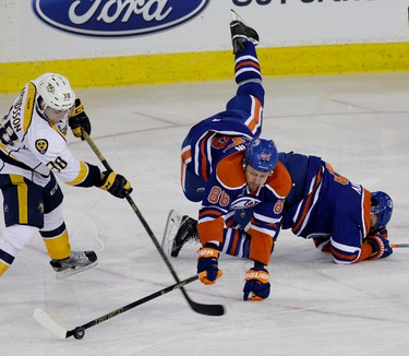 EDMONTON, ALBERTA: MARCH 14, 2016 - Edmonton Oilers defenceman Nikita Nikitin (falls over team mate Nail Yakupov as Nashville Predators winger Viktor Arvidsson (left) tries to get the puck during third period NHL hockey game action in Edmonton on Monday March 14, 2016. (PHOTO BY LARRY WONG/POSTMEDIA NETWORK)