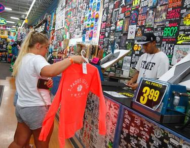 Lexi Hamilton, left, purchases a souvenir shirt from Carlos Figueroa, Thursday, March 17, 2016, at South Padre Island, Texas. Hamilton traveled to Texas from the University of Kansas for spring break. (Nathan Lambrecht/The Montior via AP)