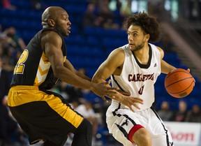 Carleton Ravens' Kaza Kajami-Keane (right) wheels around Kashrell Lawrence of the Dalhousie Tigers in their CIS men's basketball semifinal.  (Gerry Kahrmann/Postmedia Network)