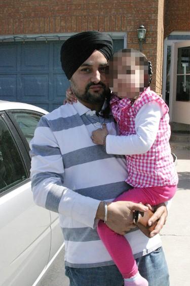 Manjinder Litt holds his daughter in 2010. (Joe Warmington/Toronto Sun)