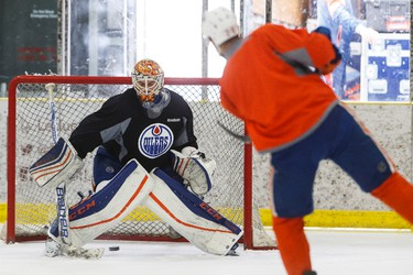 Edmonton's Darnell Nurse (25) shoots on goaltender Cam Talbot (33) during an Edmonton Oilers practice at Leduc Recreation Centre in Leduc, Alta., on Friday April 8, 2016. Photo by Ian Kucerak