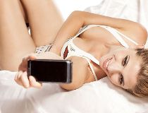 Woman talking a selfie on a bed