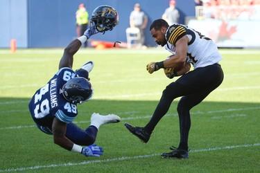 Toronto Argonauts Nicholas Williams LB (49) flies at Hamilton Tiger-Cats Junior Collins WR (87) ripping his helmet off during the second  quarter pre-season game at BMO Field  Toronto, Ont. on Saturday June 11, 2016. Jack Boland/Toronto Sun/Postmedia Network