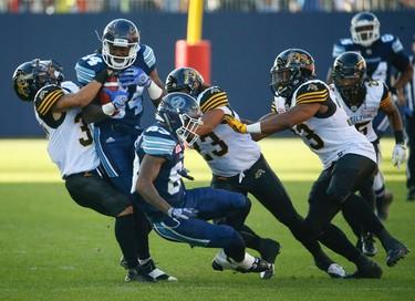 Hamilton Tiger-Cats Trey Wolfe DB (37, L) tries to drag down Toronto Argonauts Llevi Noel WR (84) during the fourth quarter pre-season game at BMO Field  Toronto, Ont. on Saturday June 11, 2016. Jack Boland/Toronto Sun/Postmedia Network