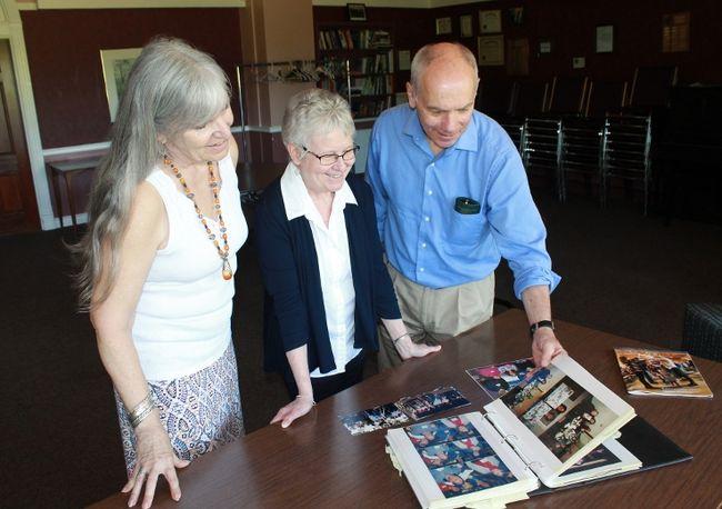 Unitarians Wendy Starr, Ann Steadman and Allan McKeown flip through a book of photographs documenting 60 years of Unitarianism in Sarnia and Port Huron.  CARL HNATYSHYN/SARNIA THIS WEEK