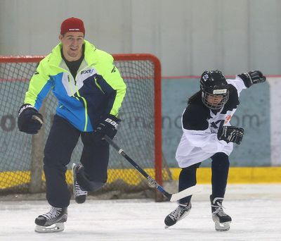 Winnipeg Jets center Mark Scheifele (l) runs through a drill with a young player during a KidSport hockey camp in Winnipeg, Man. Sunday June 26, 2016. Brian Donogh/Winnipeg Sun/Postmedia Network