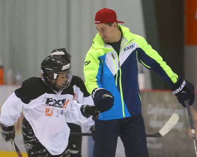 Winnipeg Jets center Mark Scheifele (r) works with young players during a KidSport hockey camp in Winnipeg, Man. Sunday June 26, 2016. Brian Donogh/Winnipeg Sun/Postmedia Network