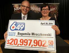 AGLC President Bill Robinson (left) presents a ceremonial cheque to Lotto 6/49 $21 million winner Bogumila Mroczkowski at the Alberta Gaming & Liquor Commission in St. Albert, on Tuesday, July 26, 2016. Ian Kucerak / Postmedia