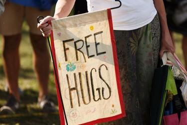 A woman holds a free hugs sign during the Edmonton Folk Music Festival at Gallagher Park in Edmonton, Alberta on Thursday, August 4, 2016. Ian Kucerak / Postmedia
