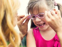 Mom putting glasses on child