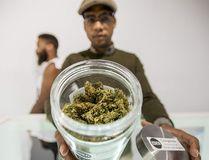 An employee showcases a large jar of marijuana on a shelf at Eden in Toronto. (Tyler Anderson/Postmedia)