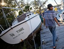 Chris Hinds walks between boats pushed up amongst the twisted docks at Palmetto Bay Marina damaged by Hurricane Matthew in Hilton Head, S.C., Sunday, Oct. 9, 2016. (AP Photo/David Goldman)